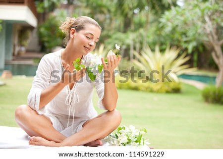 Close up view of an attractive young woman holding and smelling tropical flowers in an exotic spa garden. - stock photo