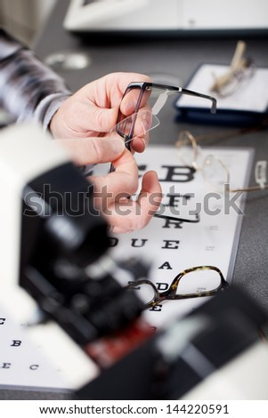 close up view of an optician repairing glasses - stock photo