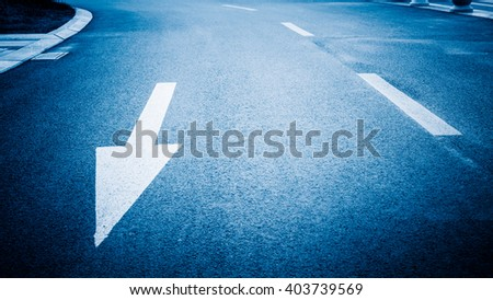 Close-up view of arrow sign on road, blue toned image. - stock photo