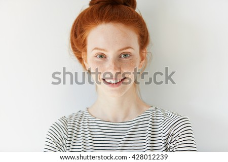 Close up view of attractive happy Caucasian woman with ginger hair and freckles wearing stylish clothes looking and smiling at the camera posing against white studio wall. Youth and happiness concept - stock photo