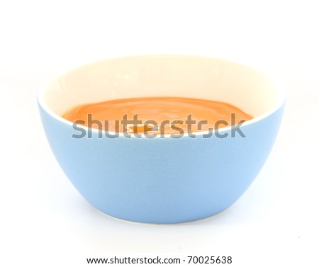 Close up view of baby orange fruit porridge / mush in blue bowl - stock photo