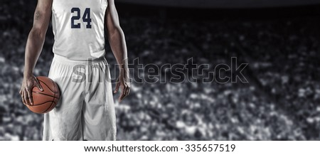 Close up view of Basketball Player in a large basketball arena. Wide angle photo with lots of copy space.