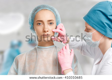 Close up view of beautiful female getting Botox facial injection in her cheek against clinic interior background. Young Caucasian woman having cosmetic procedure in beauty clinic. Aesthetic medicine - stock photo