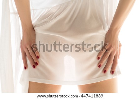 Close up view of beautiful woman bottoms and hands standing near window. Sexy woman wearing white dress and touching her legs. - stock photo