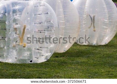 Close up view of bubble football balls on the grass.