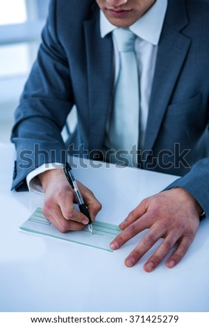 Close up view of businessman completing a cheque
