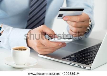 Close up view of businessman hands holding credit card and making online purchase using mobile phone. Shopping, consumerism, delivery, financial security, anti-fraud or internet banking concept. - stock photo