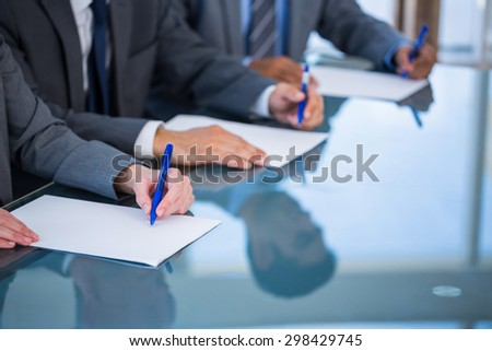 Close up view of businessman hands writing on paper in office