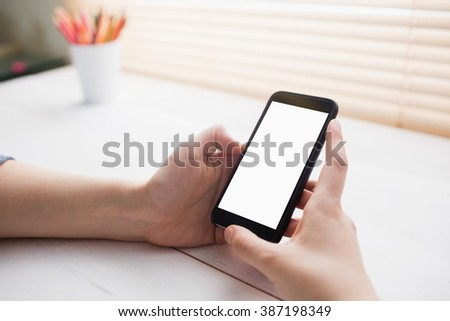 Close up view of businesswoman using her phone at her desk in office - stock photo