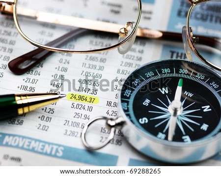 Close up view of calculator, pencil and glasses on newspaper - stock photo