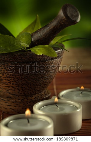 Close up view of candles, brown mortar with ingredients inside on green back