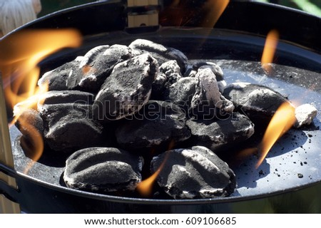 Close up view of charcoal briquettes in small barbecue with flames and ash.