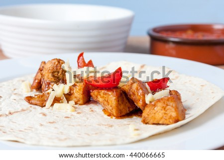 Close-up view of chicken fajita mix topped with grated cheese laying on an open flour tortilla - stock photo
