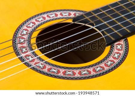 Close up view of classical guitar includes with strings, fingerboard and part of body. - stock photo