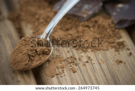 Close-up view of cocoa powder with spoon and broken dark chocolate bars on wooden background - stock photo