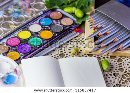Close-up view of colorful pencils and watercolor for drawing with notebook on old wooden background
