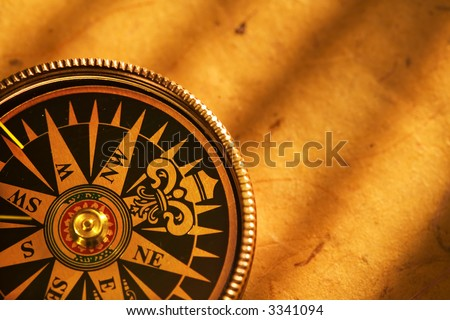 Close up view of compass on antiqua paper background - stock photo