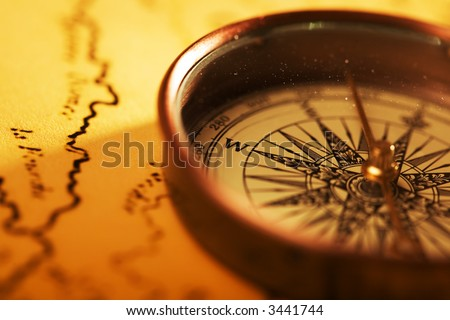 Close up view of compass on old map background - stock photo