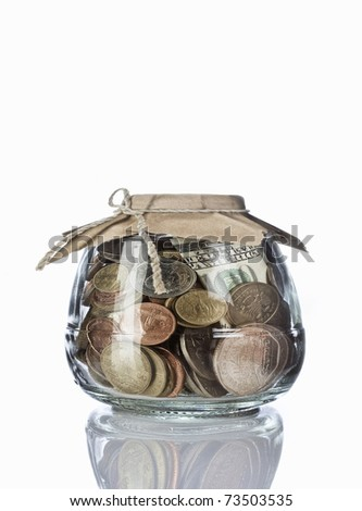 Close up view of container filled with coins on white back - stock photo