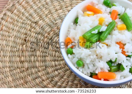 Close up view of cooked rice in bowl - with mixed of colorful vegetable on natural background - stock photo