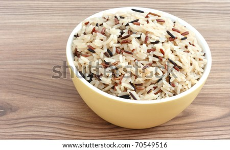 Close up view of cooked variety of rice sorts in yellow bowl - basmati and indian black on wooden background - stock photo