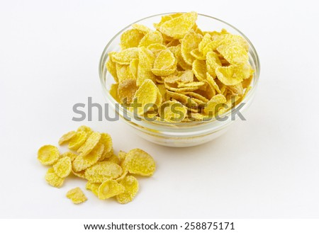 Close-up view of cornflakes in a glass bowl on white background - stock photo