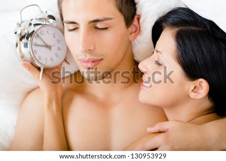 Close up view of couple lying in bedroom. Woman holds alarm clock near the ear of man, top view - stock photo