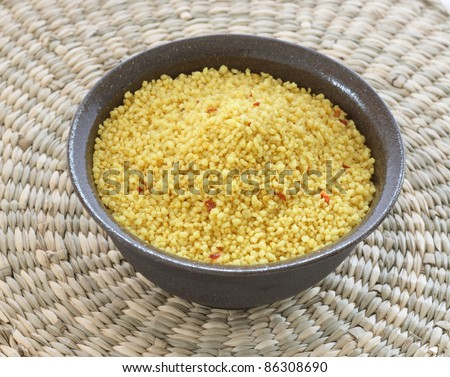 Close up view of couscous in brown bowl on natural wicker background - stock photo