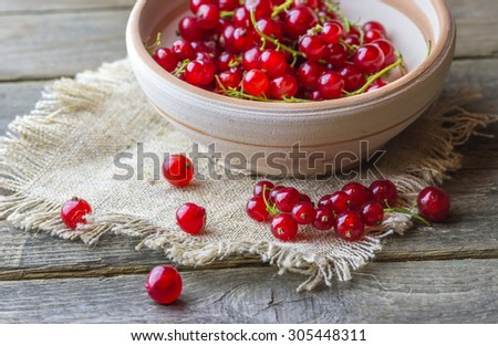Close-up view of cranberries in handmade clay plate on old wooden background - stock photo