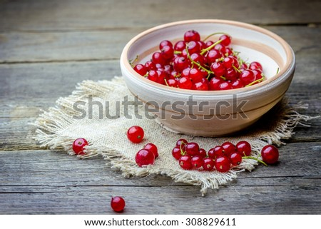 Close-up view of cranberries in handmade clay plate with sackcloth on old wooden background - stock photo