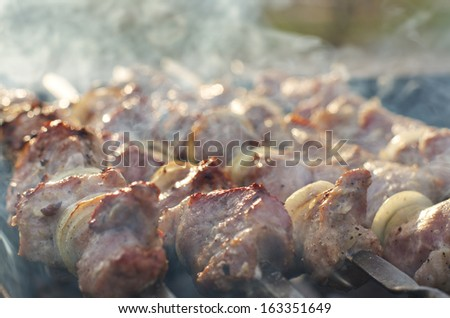 Close up view of crispy meat kebabs smoking on the grill on a BBQ while being cooked outdoors on the fire during a camping trip or picnic - stock photo