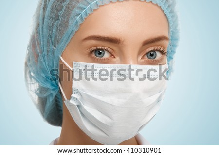 Close up view of cute Caucasian blue-eyed woman doctor wearing blue cap and white facemask looking at the camera isolated against studio background. Healthcare, medical and plastic surgery concept  - stock photo