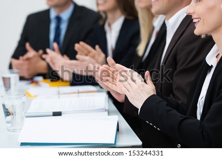 Close up view of diverse businesspeople in a meeting applauding and clapping their hands in recognition of an achievement or in praise - stock photo