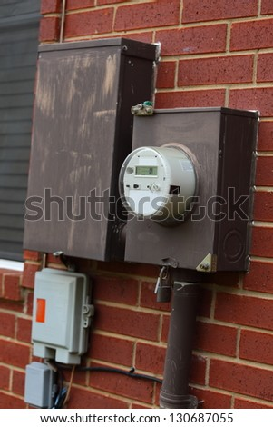 Close up view of electric and breaker boxes on the side of a house - stock photo