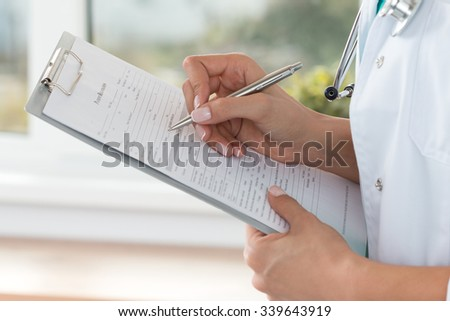 Close-up view of female doctor hands filling patient registration form. Healthcare and medical concept - stock photo