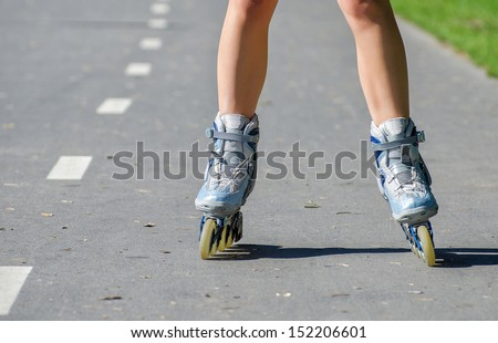 Close-up view of female legs in roller blades - stock photo