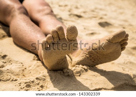 Close-up view of foot by the man lying on the sand beach - stock photo