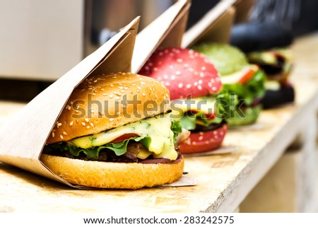 Close-up view of hamburgers with colored buns in a row on wooden background - stock photo