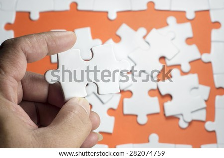 Close up view of hand holding white puzzle - stock photo