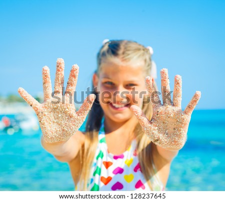 Close-up view of hands by the girl on the sand beach.