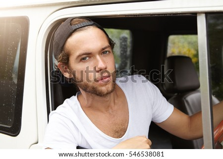 Close up view of handsome young man with stylish beard sitting on driver's seat in leather cabin of his white four-wheel drive car and looking at camera with serious expression during road trip