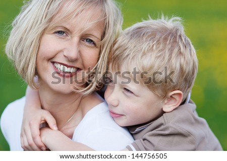 close-up view of happy mother and her son standing outside