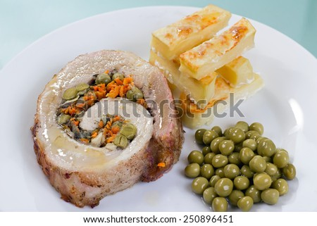 Close-up view of home meatloaf with roasted potatoes and green peas. - stock photo