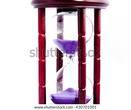 Close-up view of hourglass/sandglass/sand timer with sand falling isolated on white background. Sand flowing inside hour glass. Time constraints, limitations and deadline concept. Start and end times. - stock photo
