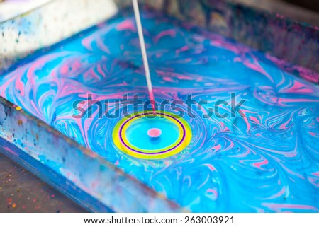 Close up view of making circle on water surface with stick and color inks - stock photo