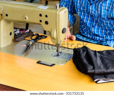 Close-up view of man hand with sewing machine in action. He is repairing a sewing black fabric on an old sewing machine - stock photo