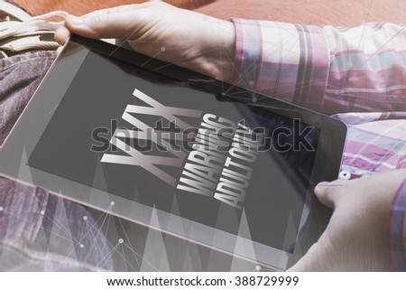 close-up view of man holding a tablet showing adult porn site. Digital porn industry concept. All screen graphics are made up.