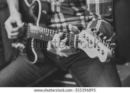 Close up view of man's hands playing electric guitar.  Black and white picture - stock photo