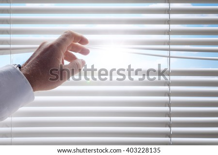 close up view of man's head spreading blinds and sunny background