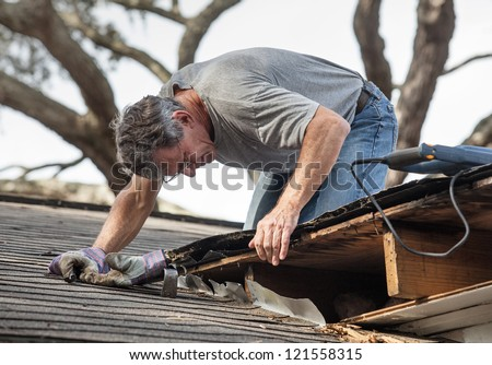 Close up view of man using removing rotten wood from leaky roof. After removing fascia boards he has discovered that the leak has extended into the beams and decking. - stock photo